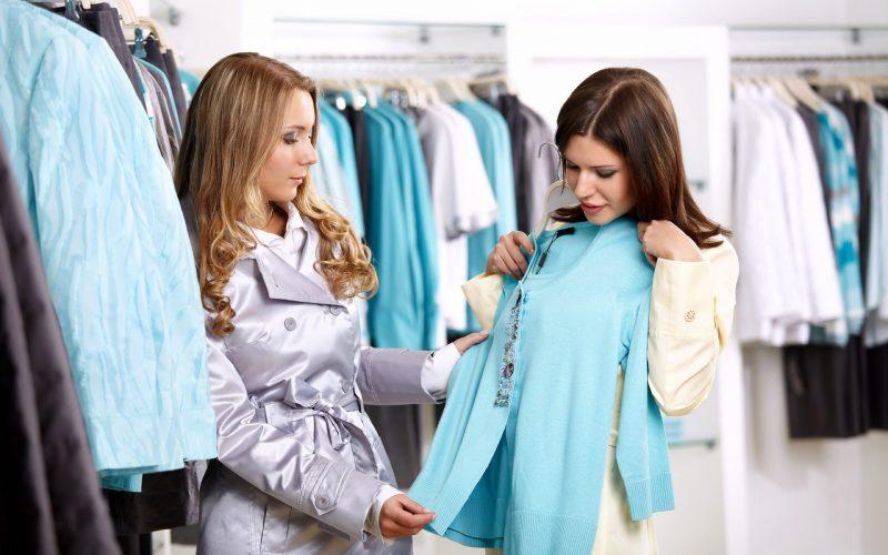 técnicas de venda: vendedora mostrando peças de roupa