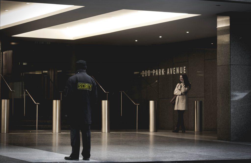 segurança de costas e mulher distante em saguão de prédio