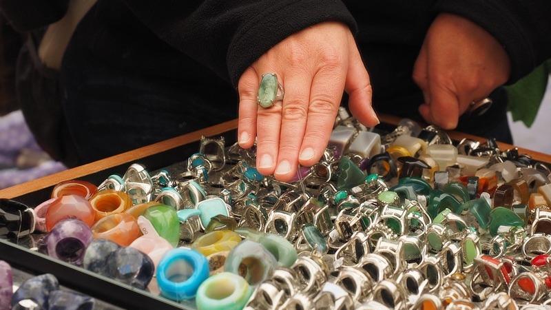 Pessoa passa a mão em mostruário com vários anéis de pedras.