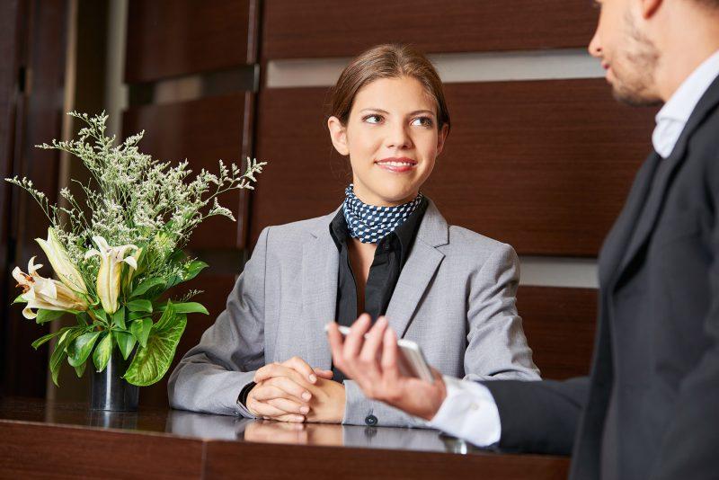 treinamento da equipe do hotel: atendente recebe hóspede em mesa