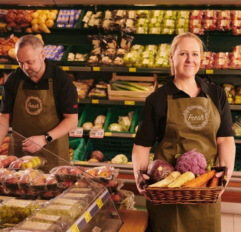 Dois colaboradores em setor de verduras usando uniformes profissionais