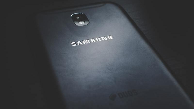 Parte traseira de um celular Samsung deitado sob uma mesa preta. A imagem é composta, também, por um efeito escuro.
