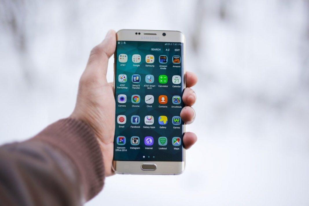 Mão de uma pessoa segurando um celular Samsung. Ele está ligado na tela inicial, em que os aplicativos ficam em evidência