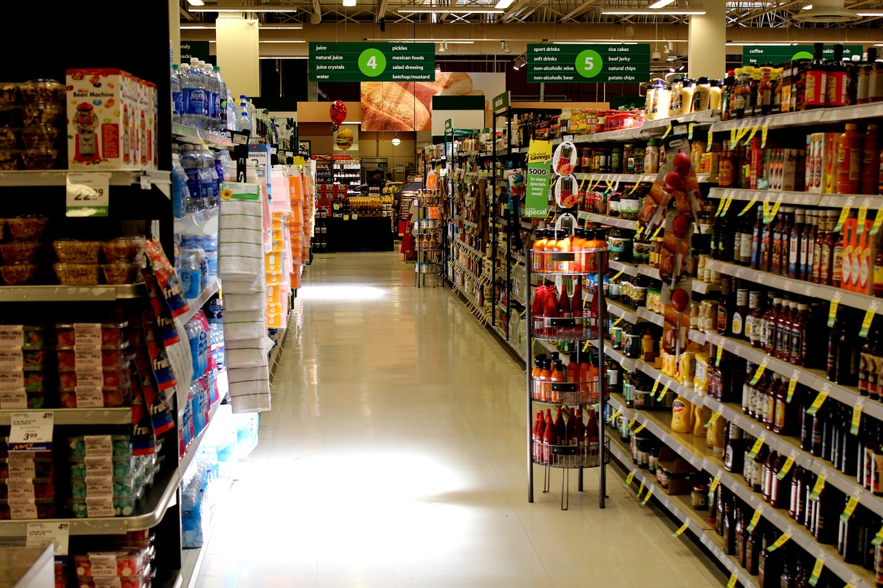 Corredor de um supermercado bem iluminado e organizado, com gôndolas cheias de produtos.