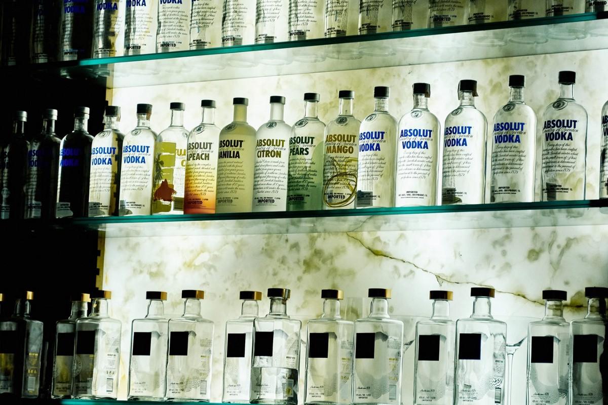 Três prateleiras de vidro com garrafas transparentes de vodca enfileiradas.