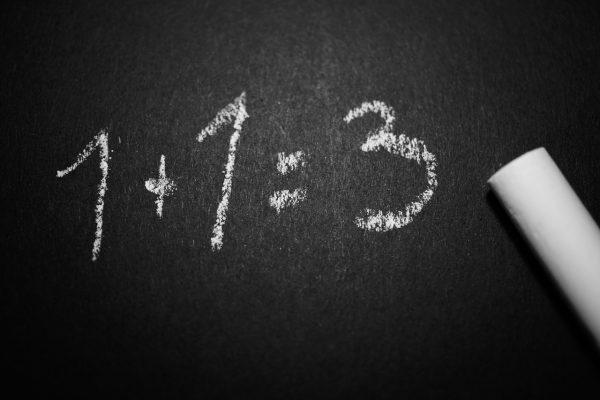 """Texto """"1+1=3"""" escrito de giz para exemplificar que o lema """"o cliente tem sempre razão"""" pode não ser tão simples assim."""
