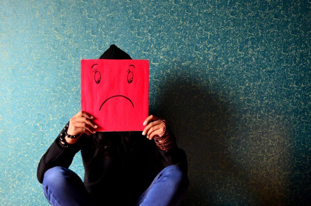 Pessoa sentada segurando um papel vermelho na frente do rosto, no qual está desenhado um rosto triste.