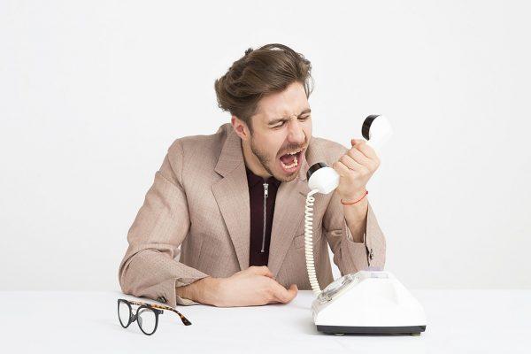 Homem de paletó sentado à mesa, segurando um telefone e gritando agressivamente com o objeto.