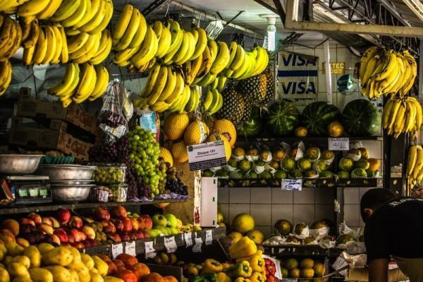 Sacolão com muitas frutas e verduras nas prateleiras. Acima, muitos cachos de bananas maduras pendurados.