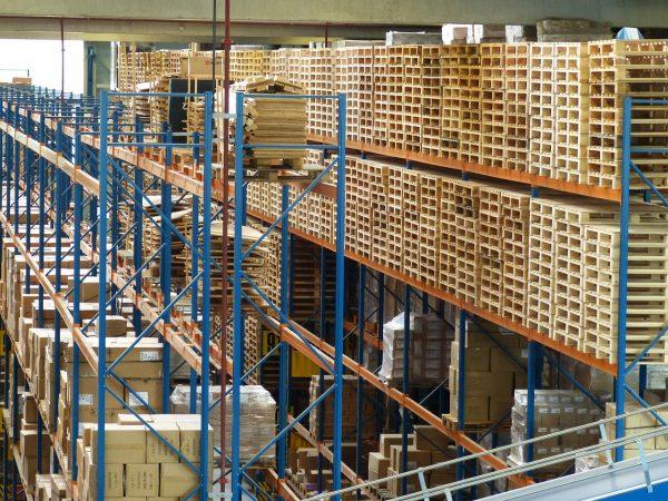 Galpão de estoque com paletes e caixas enfileiradas e empilhadas em grandes estruturas azuis.