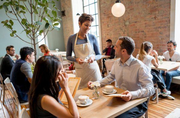 Mulher de avental, anotando pedido de dois clientes em um restaurante. Ao fundo, outras mesas com clientes.
