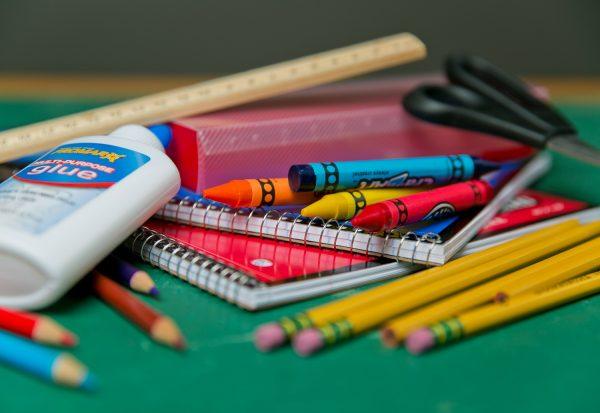 Materiais de papelaria (cola, caderno, tesoura, régua, lápis, giz de cera) para ilustrar uma das ideias de pequenos negócios