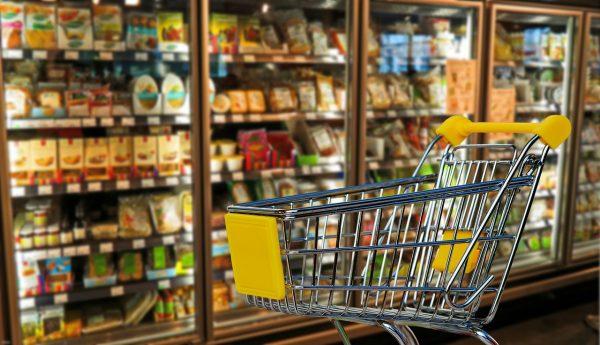Em destaque, um carrinho de mercado com detalhes amarelos. Ao fundo, geladeiras de mercado cheias e com portas de vidro.