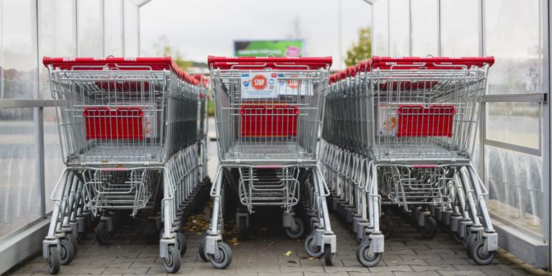 Três fileiras de carrinhos de compras de mercado cromados com detalhes vermelhos.