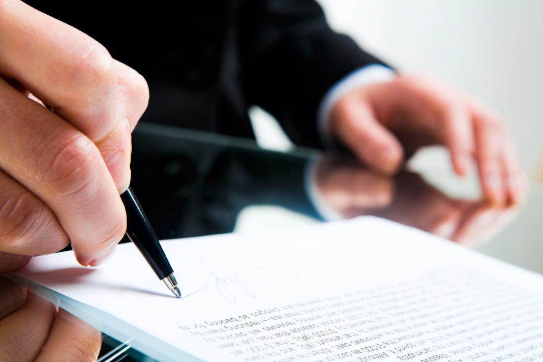 Homem assinando contrato