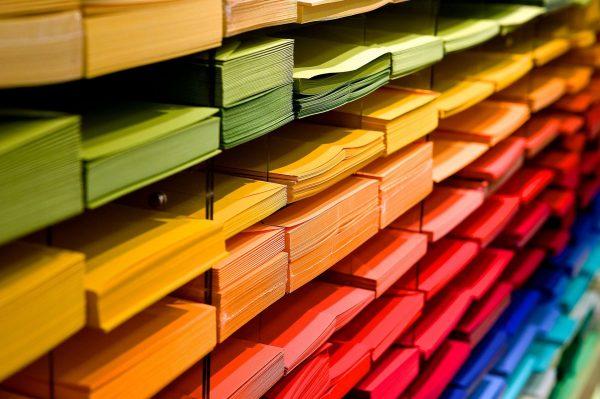 Estoque de papeis coloridos empilhados em uma prateleira.