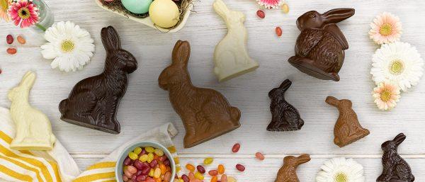 Decoração de páscoa com coelhos de chocolate sobre mesa com flores e balas.