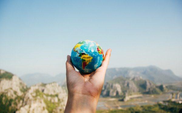 No centro, mão segurando um globo terrestre (mapa mundi) pequeno. Ao fundo, céu azul em degradê e montanhas.