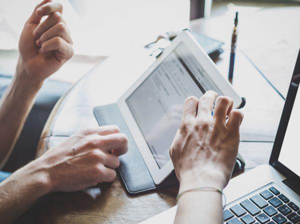 Duas pessoas usando um tablet, que está em cima da mesa. Apenas as mãos das pessoas aparecem.