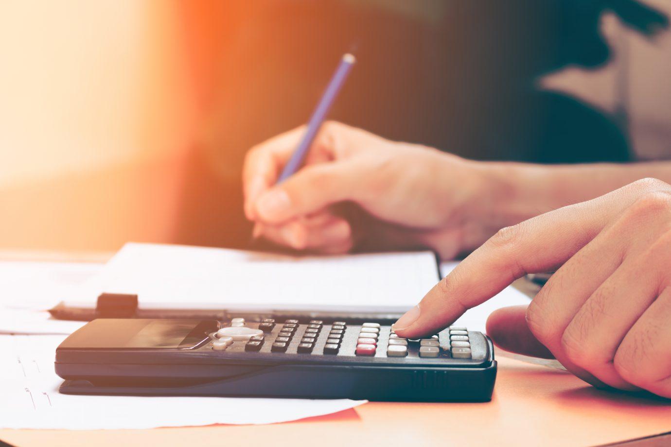 À frente, mão digitando na calculadora. Ao fundo, mão escrevendo em bloco de notas com um lápis.