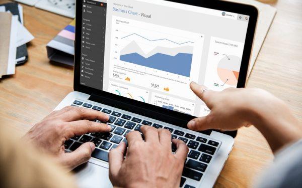 Duas mãos em cima do teclado de um notebook sobre uma mesa. Na tela, gráficos e informações. Outra mão aponta para a tela.
