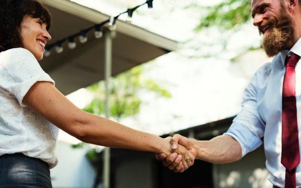 Mulher e homem dão um aperto de mãos e sorriem, representando simbolicamente o momento de pós-venda.