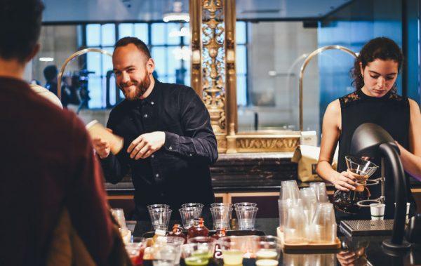 homem e mulher jovens atendem clientes e preparam bebidas em um bar.