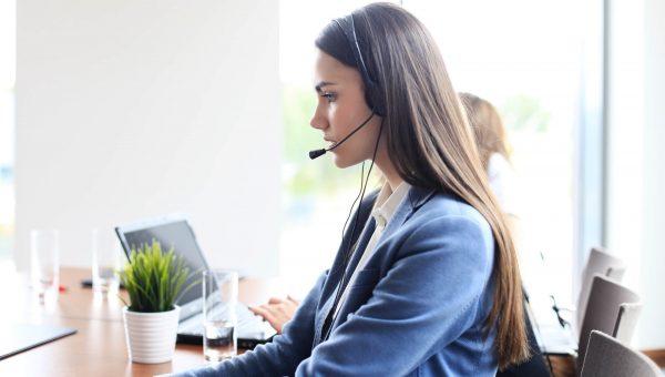 Mulher de cabelos compridos atende cliente pelo headset de telemarketing. Atrás dela, outra pessoa trabalha com notebook.