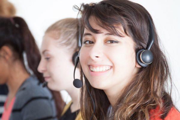 Mulher jovem sorrindo enquanto trabalha no atendimento de telemarketing junto com outras pessoas ao fundo.
