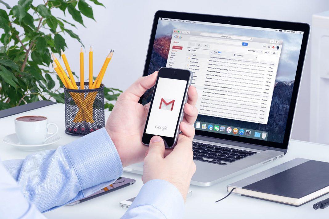 Sobre a mesa, objetos de escritório e notebook. Mãos seguram um celular. Nas telas dos aparelhos, a pessoa lê e-mails.