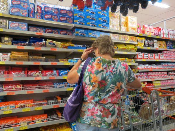 senhora escolhendo chocolates em gôndola de supermercado