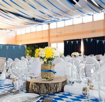 Arranjo de mesa com taças de cristal, pratos e talheres. A toalha de mesa é azul e branca.