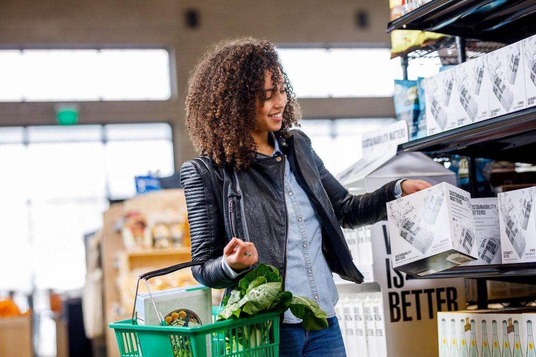 Mulher pegando um produto da prateleira de um mercado. Pendurada no braço direito dela, há uma cesta com produtos dentro.