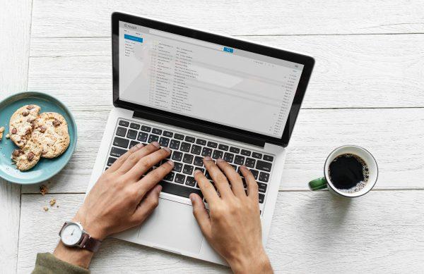 Mãos teclam mensagem de pós-venda no notebook. Do lado esquerdo, um prato com cookies; do lado direito, uma caneca de café.