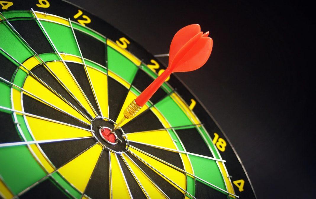 alvo nas cores preto, verde e amarelo, com um dardo vermelho prese em seu centro.