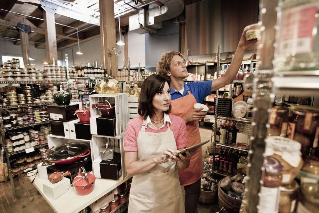 Dupla de funcionários confere produtos em gestão de compras.