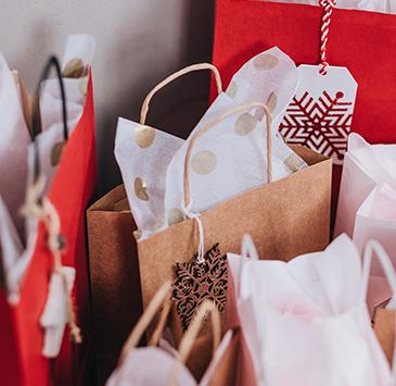 Várias sacolas de presente: algumas na cor parda, outras vermelhas; todas têm uma etiqueta na alça e papel saindo de dentro.