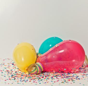 Balões com confetes em chão branco