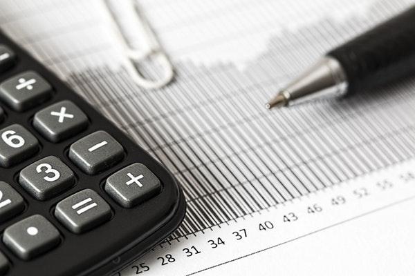 Caneta, calculadora e clips de papel sobre gráfico com numeração crescente.