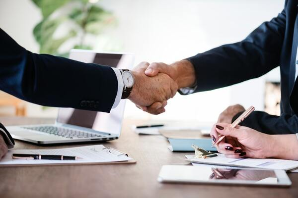Um aperto de mãos entre pessoas de terno, cada uma de um lado da mesa. Eles estão em um ambiente empresarial.
