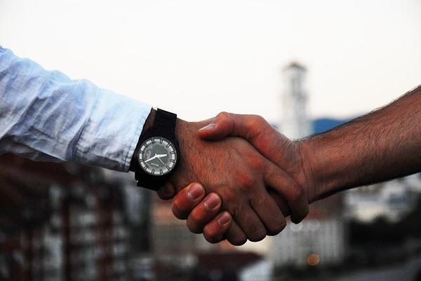 Contratar funcionário: aperto de mãos. Uma das pessoas usa uma camisa social de manga comprida e um relógio.