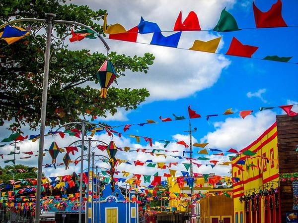 Ambiente externo com cores vibrantes e decoração de festa junina, mostrando diversas bandeirinhas penduradas em varais.