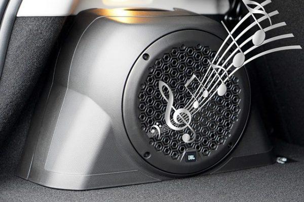 Caixa de som em um porta malas do carro com ilustração de notas musicais saindo do alto falante.