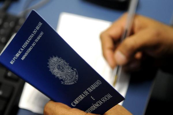 Em foco, mão segura carteira de trabalho brasileira. Ao fundo e desfocada, a outra mão escreve em um papel.