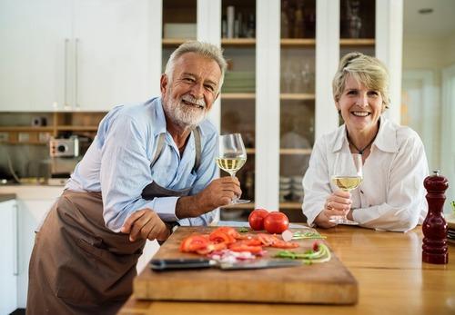 Casal tomando vinho e preparando uma refeição para o Dia dos Namorados.