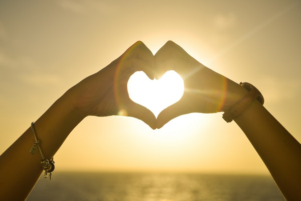 Duas pessoas formam um coração com as mãos contra o sol.