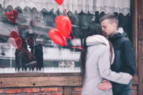 Refletidos em vitrine de loja, mulher e homem se beijam. A mulher segura balões em formato de coração.