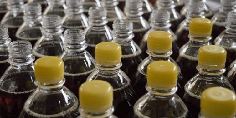 Diversas garrafas de corpo transparente enfileiradas em linha de produção. Algumas possuem tampas amarelas.