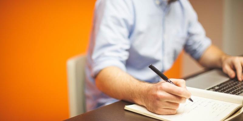 Em foco, uma mão segura caneta sobre caderno e a outra usa um notebook. A pessoa senta à mesa, mas não mostra o rosto.