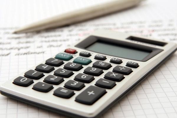 Uma calculadora em cima de uma folha de papel manuscrita.